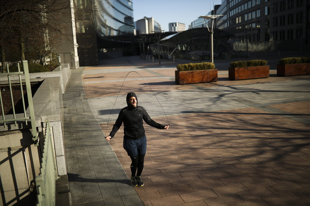 A man jumps rope as he works out in a nearly empty square outside the European Parliament during a partial lockdown ordered by Belgium government in Brussels, Monday, March 23, 2020. (Photo by Francisco Seco/AP Photo)