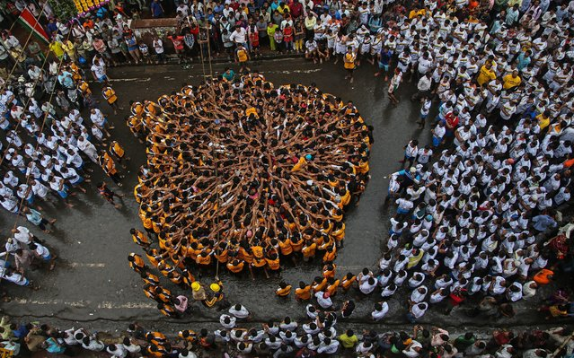 """Indian devotees pray before forming a human pyramid to reach and break a """"dahi-handi"""" (curd-pot), on occasion of the Janmashtami Festival in Mumbai, India, 18 August 2014. Hindu devotees take part in the celebration in which an earthen pot is suspended high above the ground and groups of young men and children form a human pyramid to reach the pot and break it. The festival celebrates the birth of Hindu god Lord Krishna, one of the most popular gods in Hinduism. (Photo by Divyakant Solanki/EPA)"""