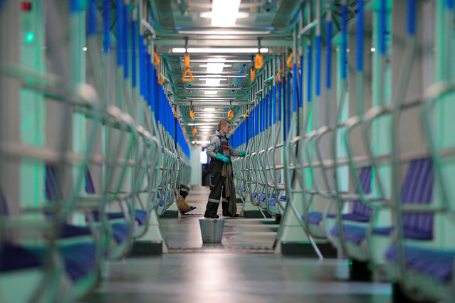 An employee wearing a protective face mask cleans and disinfects a subway train, as part of measures to prevent the spread of coronavirus (COVID-19) in Moscow, Russia on March 16, 2020. (Photo by Tatyana Makeyeva/Reuters)