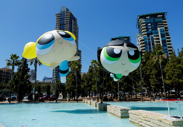 Helium-filled Powerpuff Girls figures float over a fountain as they are installed for the start of Comic-Con International in San Diego, California United States, July 20, 2016. (Photo by Mike Blake/Reuters)