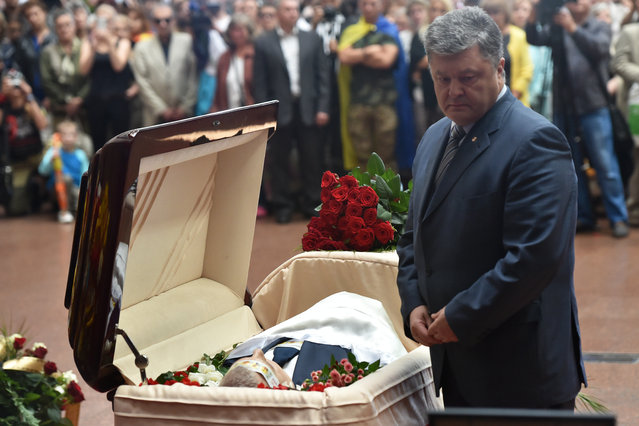 Ukrainian President Petro Poroshenko (R) pays tribute to Belarus-born journalist Pavel Sheremet, who was killed in a car bomb in central Kiev on July 20, during farevel ceremony in Ukrainian House on July 22, 2016. Hundreds of mourners shed tears and laid flowers on Friday at the open casket of a top reporter whose targeted car-bomb slaying sent shock waves through Ukraine's tight-knit journalistic community. July 20's death of Pavel Sheremet – a 44-year-old columnist for Ukrainska Pravda – came 16 years after the beheading of the investigative news site's founder that carried dark political overtones. (Photo by Sergei Supinsky/AFP Photo)