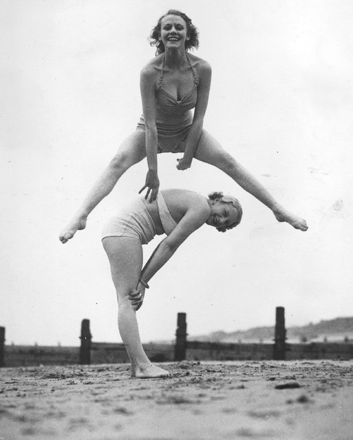 Two women enjoying a game of leap-frog on the beach at Blackpool. 28th March 1936.