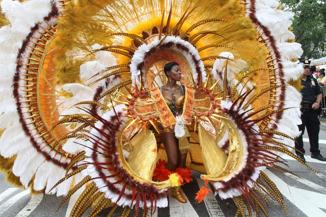 In this September 2, 2013, file photo, dressed in costume, Kelva Joseph makes her way along Eastern Parkway in the Brooklyn borough of New York during the West Indian Day Parade. The annual parade is set for Monday, September 1, 2014, in Brooklyn. It echoes traditional pre-Lenten Carnival festivities and features dancers wearing elaborate, often feathered costumes. (Photo by Tina Fineberg/AP Photo)