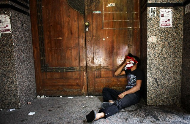A protester tries to recuperate from tear gas inhalation during clashes with police in Cairo. (Photo by Tara Todras-Whitehill/The New York Times)