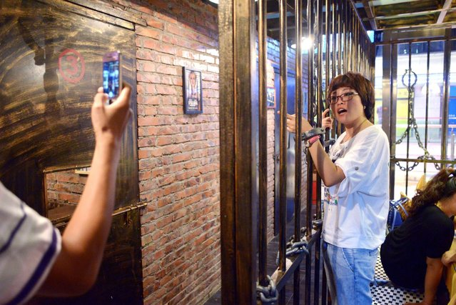 This picture taken on September 9, 2014 shows a family taking a photo before their dinner at a prison themed restaurant in Tianjin. (Photo by Wang Zhao/AFP Photo)