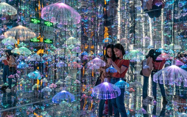 Visitors browse in the starry Art Museum. Shanghai, China, May 13, 2020. The exhibition hall uses a large number of mirror devices, combined with the layout of acousto-optic, to create a visual scene and spatial effect. (Photo by Costfoto/Barcroft Media via Getty Images)