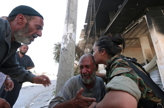 A Syria Democratic Forces (SDF) fighter comforts a civilian who was evacuated with others by the SDF from an Islamic State-controlled neighbourhood of Manbij, in Aleppo Governorate, Syria, August 12, 2016. (Photo by Rodi Said/Reuters)