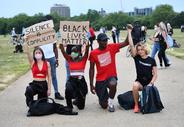 """People kneel as they hold banners in Hyde Park during a """"Black Lives Matter"""" protest following the death of George Floyd who died in police custody in Minneapolis, London, Britain, June 3, 2020. (Photo by Dylan Martinez/Reuters)"""