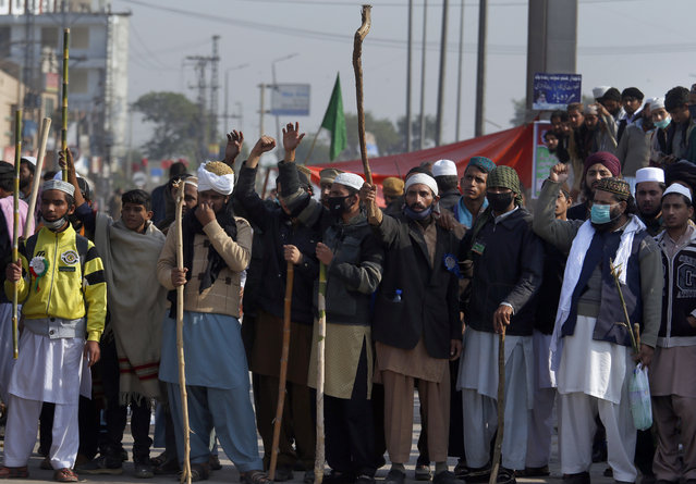Supporters of Pakistani radical religious party hold sticks while chanting slogans close to the site of sit-in protest at an intersection of Islamabad, Pakistan, Saturday, November 18, 2017. A government deadline set for an Islamic group to disband its days long rally in Pakistan's capital has expired, but authorities extended it for 24 hours to avoid a crackdown. (Photo by Anjum Naveed/AP Photo)