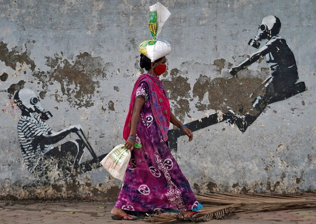 A woman wearing a protective face mask walks past a graffiti, after authorities eased lockdown restrictions that were imposed to slow the spread of the coronavirus disease (COVID-19), in Mumbai, India, June 12, 2020. (Photo by Hemanshi Kamani/Reuters)