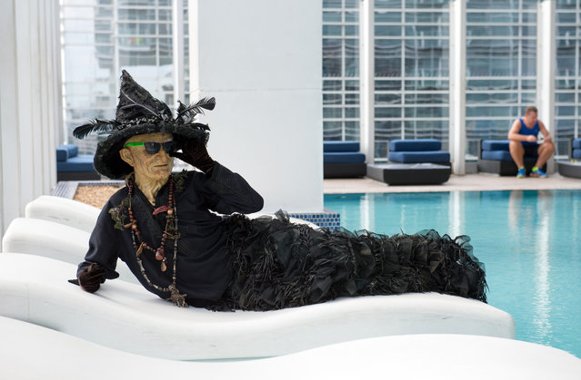Hagatha the Witch from Netherworld Haunted House with hotel guest Lonnie Austin, from England, at a swimming pool at W Atlanta Downtown hotel on Thursday, October 7, 2014. (Photo by Hyosub Shin/AJC)
