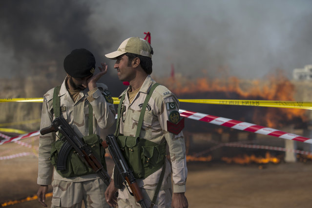 Officials of Pakistan's Anti-Narcotic Force (ANF) stand guard before a pile of confiscated drugs burned in Islamabad, Pakistan, Tuesday, December 5, 2017. Pakistan is taking strict measures to stop drug trafficking from neighboring Afghanistan and Pakistani tribal areas. (Photo by B.K. Bangash/AP Photo)