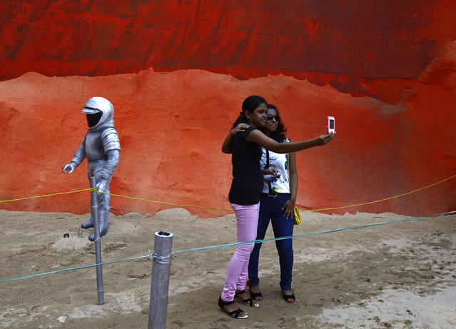 "Visitors take a selfie at a pandal, a temporary platform, with art installation titled ""Mars Mission"" as part of the Durga Puja festival in Kolkata October 1, 2014. (Photo by Rupak De Chowdhuri/Reuters)"