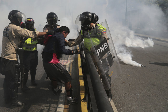 """In this May 20, 2017 file photo, Venezuelan state security forces detain a protester amid tear gas during a demonstration by opponents of President Nicolas Maduro blocking a major highway in Caracas, Venezuela. According to Human Rights Watch on Wednesday, November 29, 2017, state security forces systematically abused opposition protesters detained during months of deadly political unrest earlier this year, in what the rights group described as a level of repression """"unseen in Venezuela in recent memory"""". (Photo by Fernando Llano/AP Photo)"""