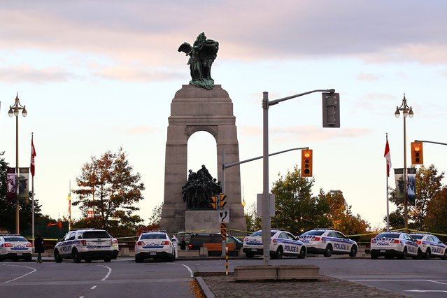 The National War Memorial is surrounded by police officers in Ottawa, Canada on Wednesday October 22, 2014 after a gunman opened fire killing a soldier before entering Parliament Hill and firing several shots in the building. Police shot dead the gunman and said an investigation was underway. (Photo by Lars Hagberg/AFP Photo)