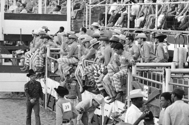To separate the convicts from the professional cowboys participating in the rodeo at the Oklahoma State Penitentiary, trousers with prison stripes are worn by the convicts, seen September 29, 1971, in McAlester, Oklahoma. Normal rodeo garb is blue shirts and denim jeans. (Photo by Eddie Adams/AP Photo)