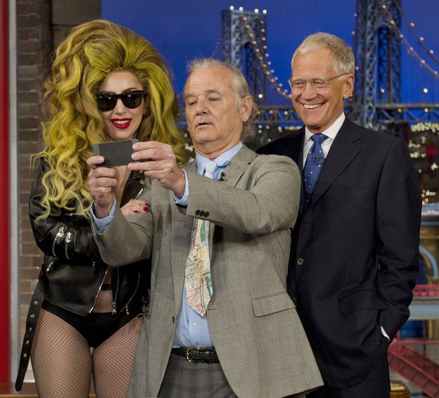 "In this photo provided by CBS, comedian Bill Murray, center, takes a ""selfie"" with singer Lady Gaga and host David Letterman on the set of the ""Late Show with David Letterman"", Wednesday, April 2, 2014, in New York. (Photo by Jeffrey R. Staab/AP Photo/CBS)"