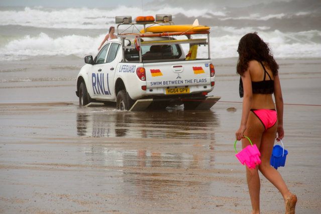 The lifeboat crew had gone out in their truck to warn beach goers about a fierce swell at Croyde Bay, Devon, southwest England on September 8, 2016. But their vehicle got stuck – prompting people to dash over and help push it out of the sand. Holidaymaker Barney Barnett, 36, captured the scene on camera. (Photo by Barney Barnett/SWNS)