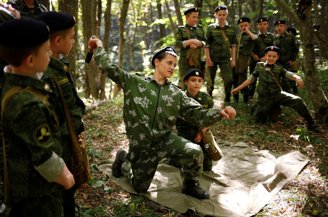 Fifth-grade students of the General Yermolov Cadet School, instructed by a tenth-grader, learn how to throw a dummy grenade during their first military tactical exercise on the ground, which includes radiation resistance classes, forest survival studies and other activities, in Stavropol, Russia, September 10, 2016. (Photo by Eduard Korniyenko/Reuters)
