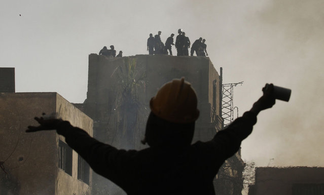 An Egyptian protester gestures towards riot police during a demonstration in Cairo's Tahrir Square on January 26, 2013. (Photo by Mohammed Abed/AFP Photo/The Atlantic)