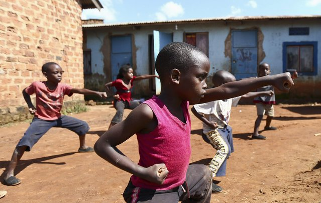 Children rehearse for their movie roles during a martial arts class organised by local non-governmental organisations (NGOs) and residents, in the Wakaliga slums of Uganda's capital Kampala, November 1, 2014. (Photo by Edward Echwalu/Reuters)