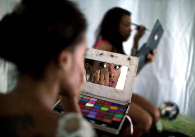 Samba dancer Diana Prado applies makeup before the start of a carnival parade at central station in Rio de Janeiro. Prado made her Carnival debut at age 19, after auditioning for a spot with the Sao Clemente, one of 13 top-tier schools that will compete for the annual titles at Rio's Sambadrome this weekend. (Photo by Felipe Dana/Associated Press)