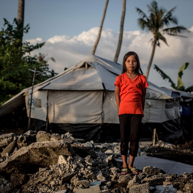 Typhoon Haiyan survivor Alma Dela Cruz stands amongst the ruins of her family home on November 6, 2014 in San Jose, Leyte, Philippines. Alma lives in the tent with six of her family members they are currently constructing a house in another area and are waiting for it to be completed. (Photo by Chris McGrath/Getty Images)