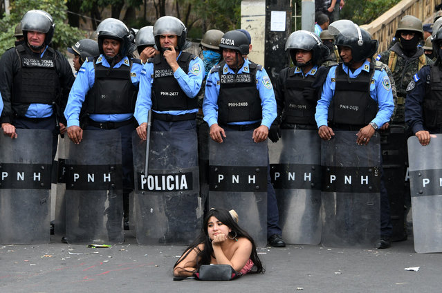 """A supporter of the presidential candidate for the Honduran Opposition Alliance Against the Dictatorship for the past election, Salvador Nasralla, lies on the street in front of police officers during a demonstration against the contested re-election of President Juan Orlando Hernandez, in Tegucigalpa, Honduras on January 21, 2018. The opposition called for a """"national strike"""" on Saturday to focus on blocking the country's main roads ahead of the start of the president's new term in office on January 27. Dozens of people have been killed and hundreds jailed since Hernandez was declared the winner of the November 26 run-off election – but only after a three week stretch of often-interrupted ballot counting that stoked tensions and sparked accusations of fraud in the Central American country. (Photo by Orlando Sierra/AFP Photo)"""
