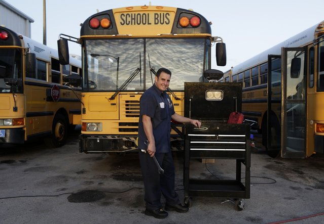 Former Cuban rafter Hanoi Lopez, 39, poses in the yard where he works as mechanic at a public school bus company in Miami, September 15, 2014. (Photo by Rolando Pujol Rodriguez/Reuters)