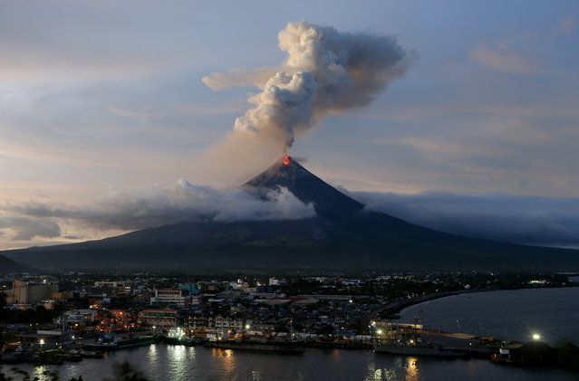 With Legazpi city in foreground, Mayon volcano erupts anew at dusk Thursday, January 25, 2018 in Albay province around 200 miles (340 kilometers) southeast of Manila, Philippines. The Philippine Institute of Volcanology and Seismology said lava flows had advanced more than a kilometer (0.6 miles) and superheated gas and volcanic debris known as pyroclastic flows had reached 5 kilometers (3 miles) from the crater in one area. Mayon's lava fountaining has flowed up to 3 kilometers (1.86 miles) from the crater in a dazzling but increasingly dangerous eruption. (Photo by Bullit Marquez/AP Photo)