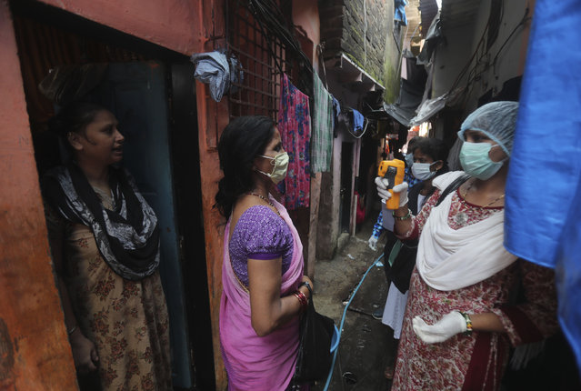 A health worker screens people for symptoms of COVID-19 in Dharavi, one of Asia's biggest slums, in Mumbai, India, Friday, September 4, 2020. The number of people infected with the coronavirus in India rose by another 80,000 and is near Brazil's total, the second-highest in the world. (Photo by Rafiq Maqbool/AP Photo)