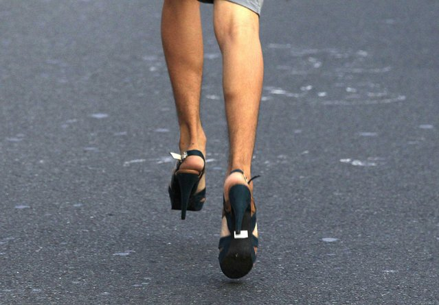 A participant wearing stilettos runs as he competes in the annual Tour De Takong, or the Stiletto race, along an avenue well-known for shoe shops, in Marikina, east of Manila November 13, 2014. The Stiletto race is part of the yearly sapatos (shoes) festival in Marikina, which locals say is the shoe capital of the Philippines. (Photo by Romeo Ranoco/Reuters)