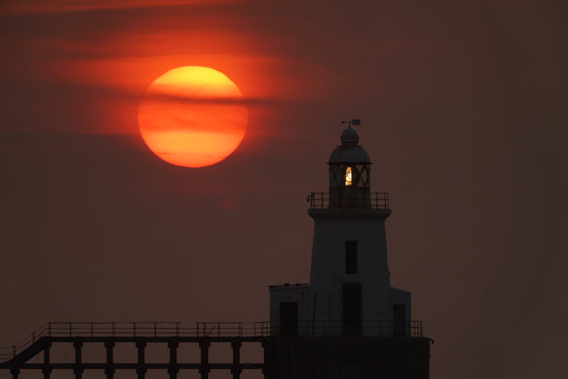 The sun rises behind Blyth East Pier Lighthouse in Northumberland, England on August 11, 2020. (Photo by Owen Humphreys/PA Images via Getty Images)