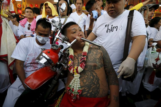 A devotee of the Chinese Bang Neow shrine pierces a motorcycle handlebar through his cheeks before a procession celebrating the annual vegetarian festival in Phuket, Thailand October 18, 2015. The festival, featuring face-piercing, spirit mediums and strict vegetarianism celebrates the local Chinese community's belief that abstinence from meat and various stimulants during the ninth lunar month of the Chinese calendar will help them obtain good health and peace of mind. (Photo by Jorge Silva/Reuters)