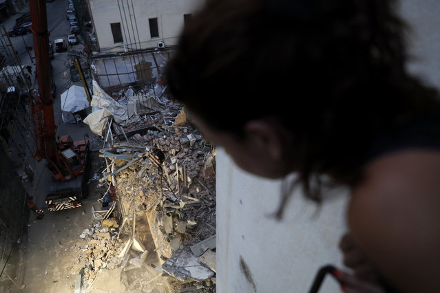 A woman watches from her apartment balcony as a crane removes the rubble of a building after a Chilean rescue team getting signals there may be a survivor at the site in Beirut, Lebanon, Early Friday, September 4, 2020. A pulsing signal was detected Thursday from under the rubble of a Beirut building that collapsed during the horrific port explosion in the Lebanese capital last month, raising hopes there may be a survivor still buried there. (Photo by Hussein Malla/AP Photo)