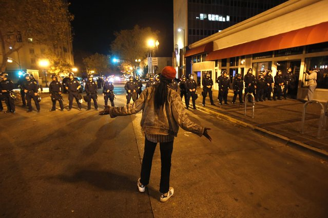 A demonstrator chants at a line of police officers during a demonstration, following the grand jury decision in the Ferguson, Missouri shooting of Michael Brown, in Oakland, California November 24, 2014. (Photo by Stephen Lam/Reuters)