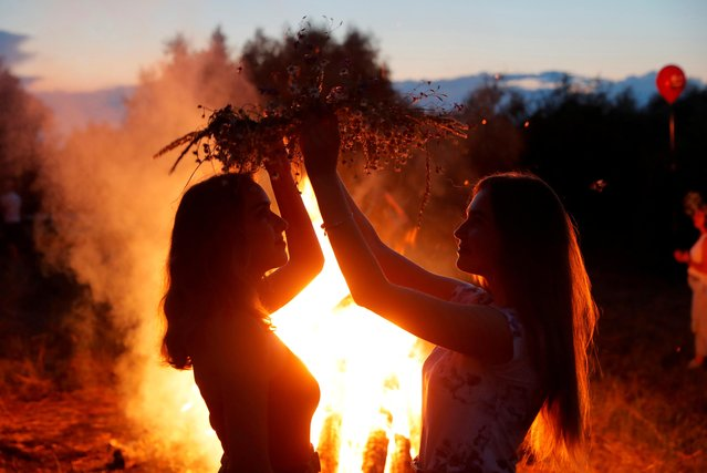 Women take part in the Ivan Kupala festival in the town of Turov, Belarus, July 6, 2020. The ancient tradition, originating from pagan times, is usually marked with grand overnight festivities – people sing and dance around campfires, believing it will purge them of their sins and make them healthier. (Photo by Vasily Fedosenko/Reuters)