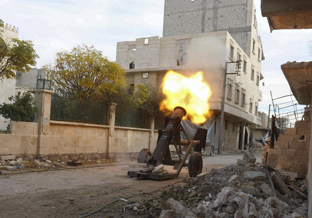 Rebel fighters launch a locally made weapon on the Karm al-Tarab frontline towards forces loyal to Syria's President Bashar al-Asaad, at Aleppo International airport November 23, 2014. (Photo by Abdalrhman Ismail/Reuters)