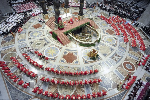 In this photo provided by the Vatican newspaper L'Osservatore Romano, cardinals, in red, attend a Mass for the election of a new pope celebrated by Cardinal Angelo Sodano, figure at the center of the stage beneath the Bernini baldachin, inside St. Peter's Basilica, at the Vatican, Tuesday, March 12, 2013. Cardinals enter the Sistine Chapel on Tuesday to elect the next pope amid more upheaval and uncertainty than the Catholic Church has seen in decades: There's no front-runner, no indication how long voting will last and no sense that a single man has what it takes to fix the many problems. (Photo by L'Osservatore Romano, ho/AP Photo)