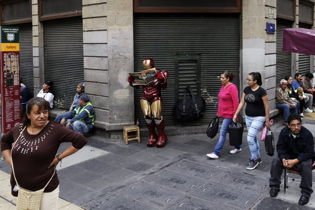 A person dressed as the superhero comic book character Iron Man reads a newspaper as pedestrians walk past in downtown Mexico City November 21, 2014. (Photo by Carlos Jasso/Reuters)