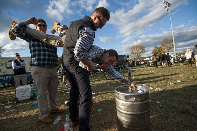 A man is held by friends as he drinks from a beer keg at the Far Hills Race Day at Moorland Farms in Far Hills, New Jersey, October 17, 2015. (Photo by Stephanie Keith/Reuters)