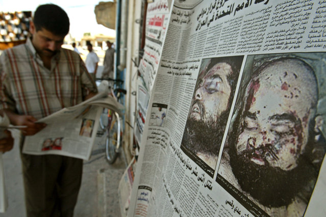 A man reads an Iraqi newspaper in the northern town of Tikrit after morgue photos of Saddam Hussein's sons Uday and Qusay were published for the first time, on July 26, 2003. Hoping to convince Iraqis that the two men were dead, the U.S. military released photos of the pair on Thursday and allowed a small group of media to view the bodies. (Photo by Faleh Kheiber/Reuters/The Atlantic)