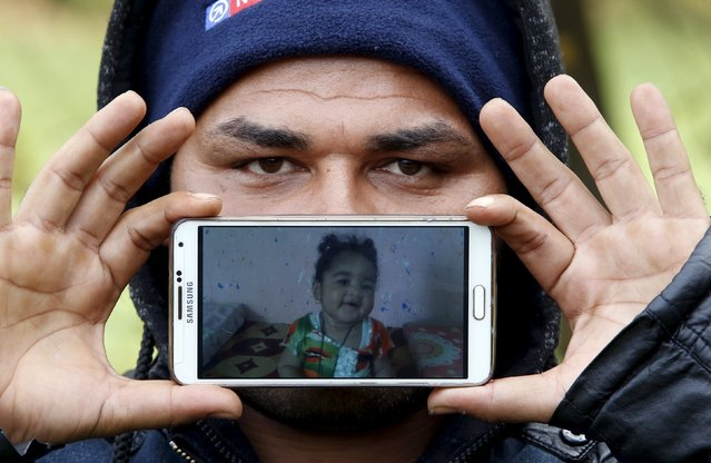 Migrant Nazar from Basrah Madina, Iraq, shows a picture of his daughter Shehed as he waits to cross the Slovenia-Austria border in Sentilj, Slovenia October 25, 2015. (Photo by Srdjan Zivulovic/Reuters)