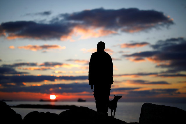 A man watches the sunset with his dog on a breakwater, along the shore of the Mediterranean Sea in Ashkelon, Israel January 9, 2018. (Photo by Amir Cohen/Reuters)