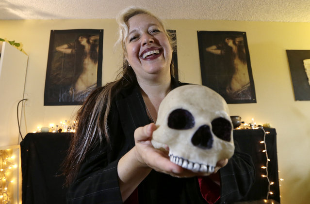 Lilith Starr, chapter head of The Satanic Temple of Seattle, holds a plastic skull while being photographed in her home Wednesday, October 28, 2015, in Seattle. At the invitation of the Bremerton High School senior class president, Starr says that her group of self-described Satanists will attend the school's football game Thursday to protest a decision by a Christian coach to continue praying at the 50-yard line after games. (Photo by Elaine Thompson/AP Photo)
