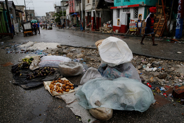 A street seller protects herself from the rain with plastics while Hurricane Matthew approaches in Port-au-Prince, Haiti October 3, 2016. (Photo by Carlos Garcia Rawlins/Reuters)