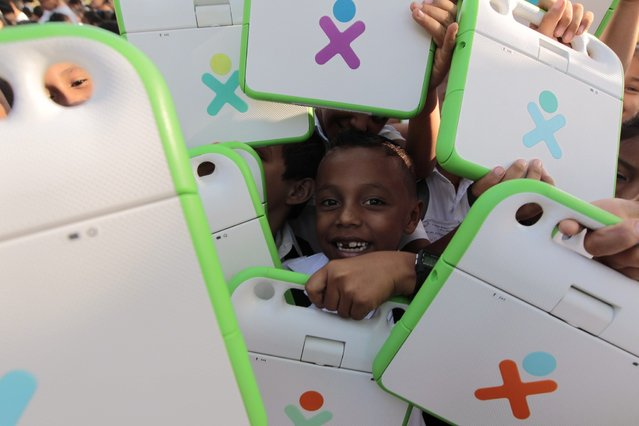 Schoolchildren hold their XO laptop at the Municipal Stadium in Ciudad Sandino, on the outskirts of Managua, April 4, 2013. Around 3,000 schoolchildren will benefit from the delivery of the laptops, which were donated by the Zamora-Teran Foundation. (Photo by Oswaldo Rivas/Reuters)