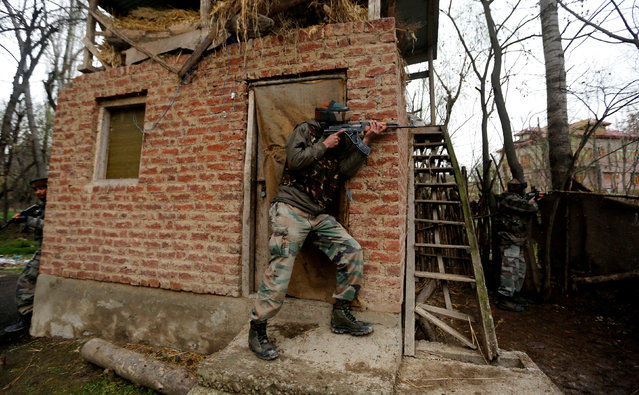 Indian Army soldiers take their positions near the site of a gunbattle, where according to local media suspected militants are holed up, on the outskirts of Srinagar March 15, 2018. A gunfight broke out between suspected militants and government forces at Balhama area of Khanmoh in outskirts of Srinagar city. A cordon- and- search- operation was launched in the area following a militant attack on a Bharatiya Janata Party (BJP) leader that left a policeman injured, officials said. (Photo by Danish Ismail/Reuters)