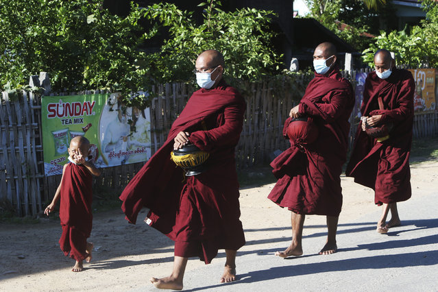 Buddhist monks wearing face masks walk on a street to collect alms in Naypyitaw, Myanmar, Friday, November 6, 2020. Myanmar's citizens go to the polls Sunday in an effort to sustain the fledgling democracy they helped install just five years ago. (Photo by Aung Shine Oo/AP Photo)