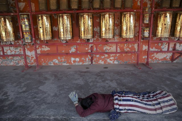 An ethnic Tibetan woman prostrates herself in front of prayer wheels as she circles around a monastery above the Larung Wuming Buddhist Institute, located some 3700 to 4000 metres above the sea level, in remote Sertar county, Garze Tibetan Autonomous Prefecture, Sichuan province, China November 1, 2015. (Photo by Damir Sagolj/Reuters)